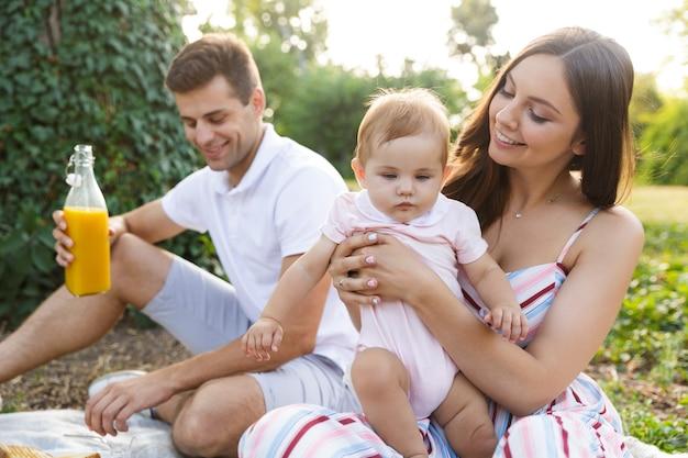 Hübsche junge familie mit kleinem baby, das zeit verbringt