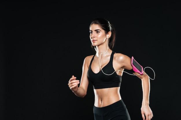 Hübsche junge fitness-dame im fitnessstudio, die über die schwarze wand läuft und beiseite schaut, während sie musik mit kopfhörern hört