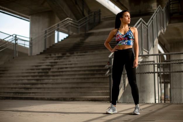 Hübsche junge fitnessfrau, die eine pause vom laufen in der städtischen umgebung macht