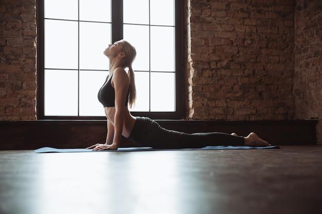 Hübsche junge fitnessfrau, die yogaübungen macht