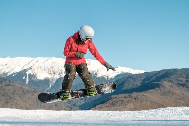 Hübsche junge frau auf dem snowboard, das über den hang springt