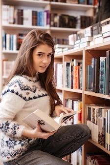 Hübsche junge frau auf der suche nach büchern in einem bücherregal in der bibliothek