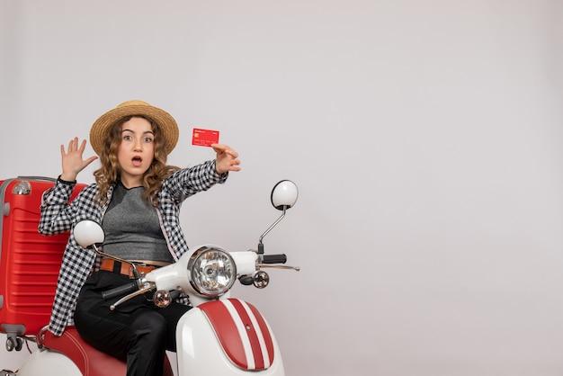 Hübsche junge frau auf moped, die karte auf grauem isoliert hochhält