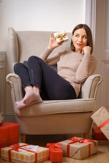 Hübsche junge frau beim sitzen in einem bequemen sessel, der eine geschenkbox hält, die von geschenken zu hause umgeben ist.