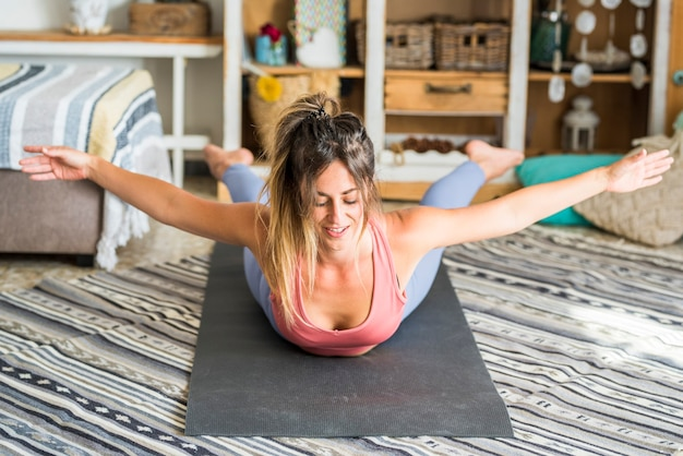 Hübsche junge frau des gesunden lebensstils machen fitness-training zu hause auf der matte glückliche weibliche sportliche menschen in ausgeglichener pilates-position lächeln und genießen aktive tägliche sitzung