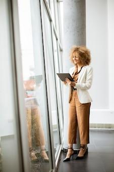 Hübsche junge frau des lockigen haares, die digitales tablett im modernen büro hält