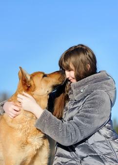 Hübsche junge frau des porträts, ihren hund des guten freunds küssend