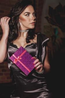 Hübsche junge frau des porträts mit geschenkbox im nachtrestaurant. frau ist überrascht. konzept, den valentinstag in einer intimen umgebung zu feiern. romantisches geschenk für ihre liebsten. platz kopieren