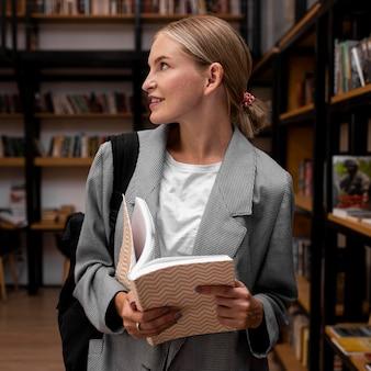 Hübsche junge frau, die an der bibliothek aufwirft