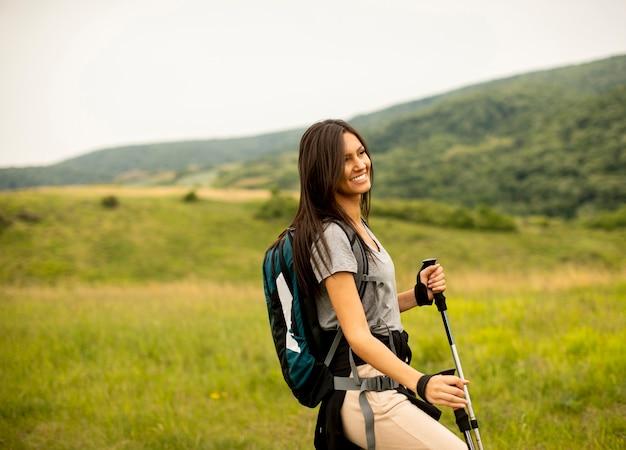 Hübsche junge frau, die an einem sommertag mit rucksack auf grünen hügeln spaziert