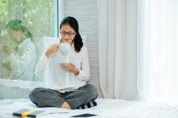 Hübsche junge frau, die auf bett sitzt und ersten morgenkaffee auf sonnenschein genießt