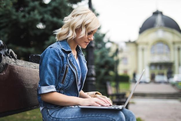 Hübsche junge frau, die auf der bank sitzt und telefon und laptop im herbstmorgen der stadt benutzt