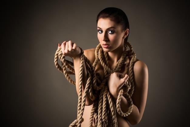 Hübsche junge frau, die auf einem grauen hintergrund aufwirft, der in ein seil gewickelt wird, während ihr nackter körper. konzept von sexualität und provokation. platz für werbung