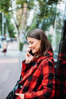 Hübsche junge frau, die auf glas auf der straße mit telefon steht