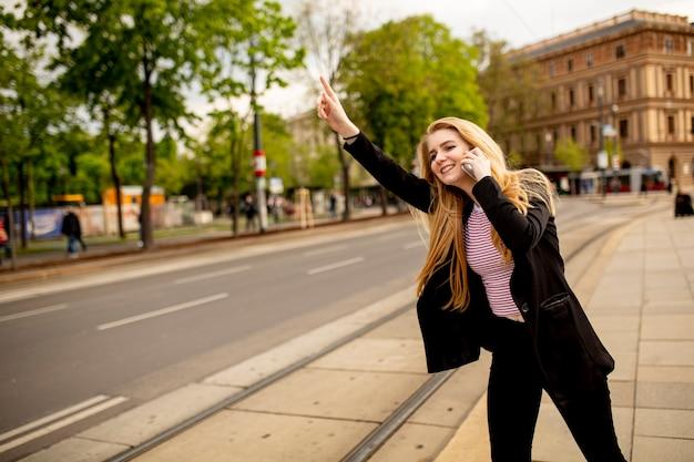 Hübsche junge frau, die auf seite der straße mit handy steht und für taxi winkt