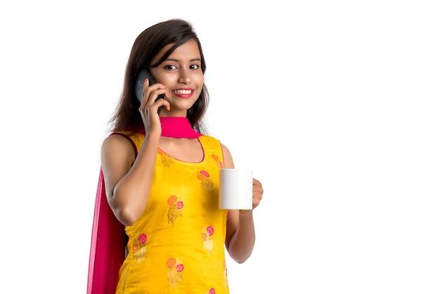Hübsche junge frau, die auf smartphone-gerät anruft, während sie leckeres kaffee- oder teegetränk trinkt
