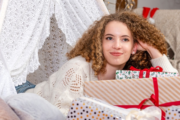 Hübsche junge frau, die auf weihnachtsgeschenkkästen liegt, tragen weißen gestrickten pullover