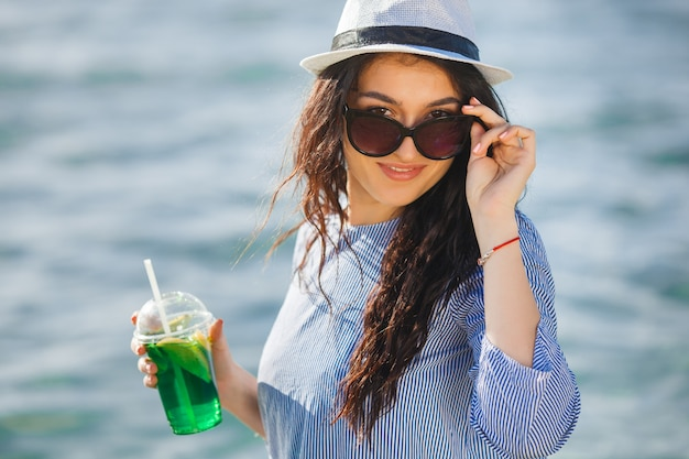 Hübsche junge frau, die cocktail am strand trinkt. attraktives mädchen, das einen drink anbietet. schöne frau, die limonade trinkt
