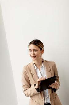 Hübsche junge frau, die digitales tablet im modernen büro hält