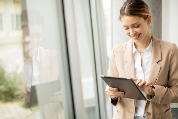 Hübsche junge frau, die digitales tablett im modernen büro hält