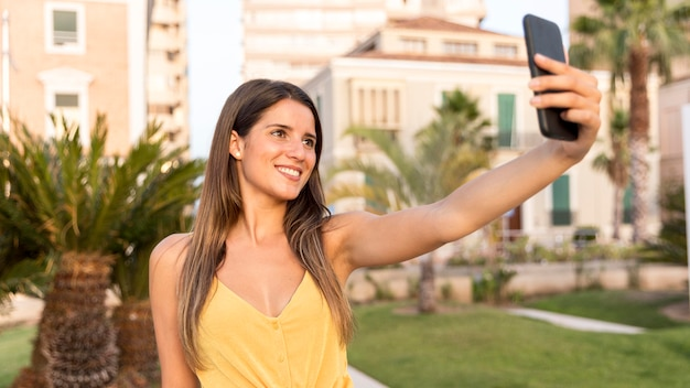 Hübsche junge frau, die ein selfie im freien nimmt