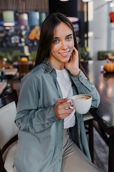 Hübsche junge frau, die eine kaffeetasse genießt