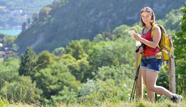 Hübsche junge frau, die eine karte in den französischen alpenbergen sucht