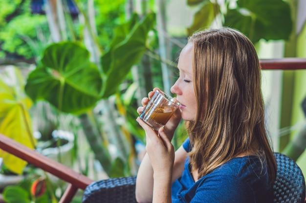 Hübsche junge frau, die eine tasse heißen zitrus-tee oder heiße limonade hält
