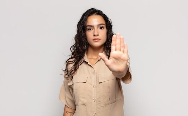 Hübsche junge frau, die ernst, streng, unzufrieden und wütend aussieht und offene handfläche zeigt, die stoppgeste macht