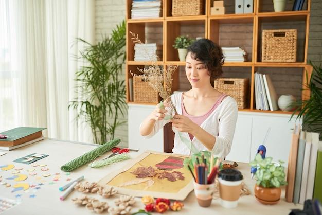 Hübsche junge frau, die es genießt, kunstwerke im japanischen kunststil namens oshibana zu machen?