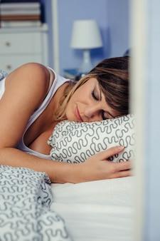 Hübsche junge frau, die friedlich im bett schläft