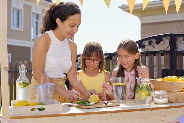 Hübsche junge frau, die frische zitronen und limetten auf holzbrett schneidet, während sie ihren zwei kleinen töchtern zeigt, wie man limonade zubereitet