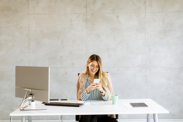 Hübsche junge frau, die handy benutzt, während sie am schreibtisch im büro sitzt