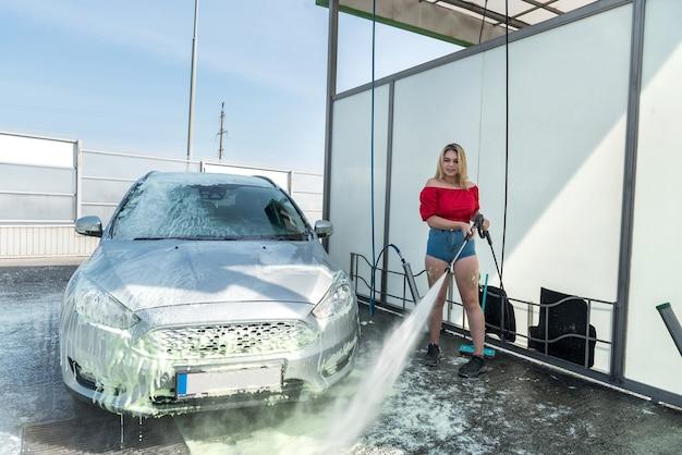 Hübsche junge frau, die ihr auto in einer selbstbedienungs-autowaschstation wäscht