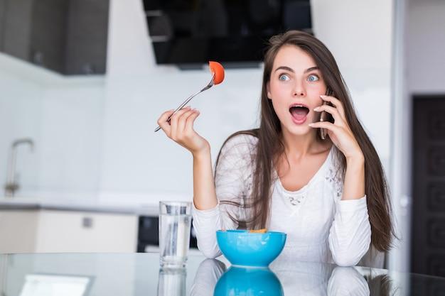 Hübsche junge frau, die ihr handy benutzt, während sie salat in der küche zu hause isst.
