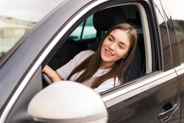 Hübsche junge frau, die ihr neues auto auf der straße fährt