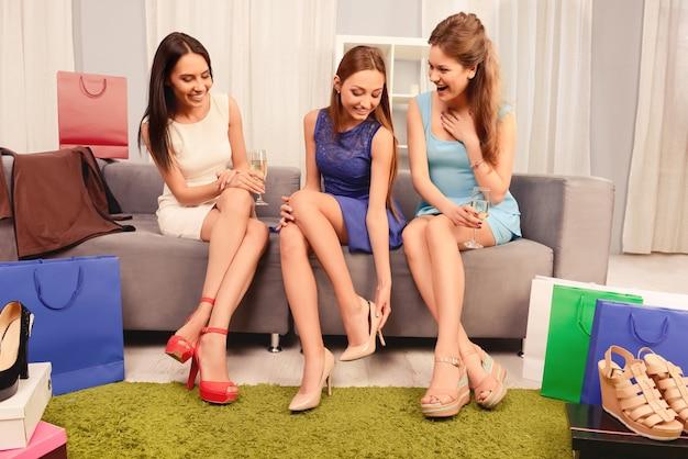 Hübsche junge frau, die ihren freundinnen ihre neuen schuhe vorführt