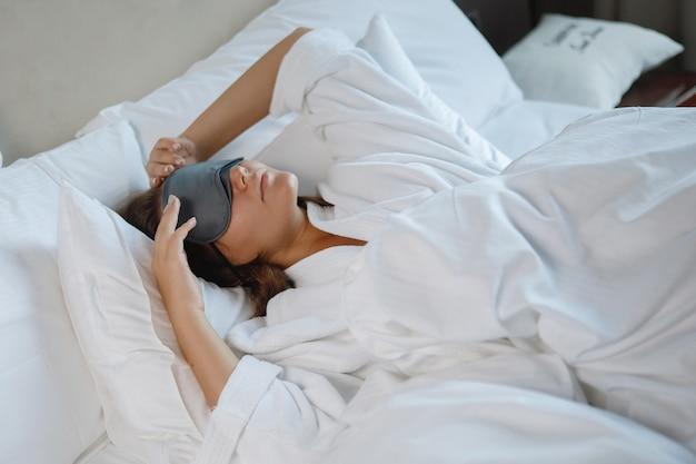 Hübsche junge frau, die in einem weißen bett mit einer schlafmaske auf ihrem gesicht schläft
