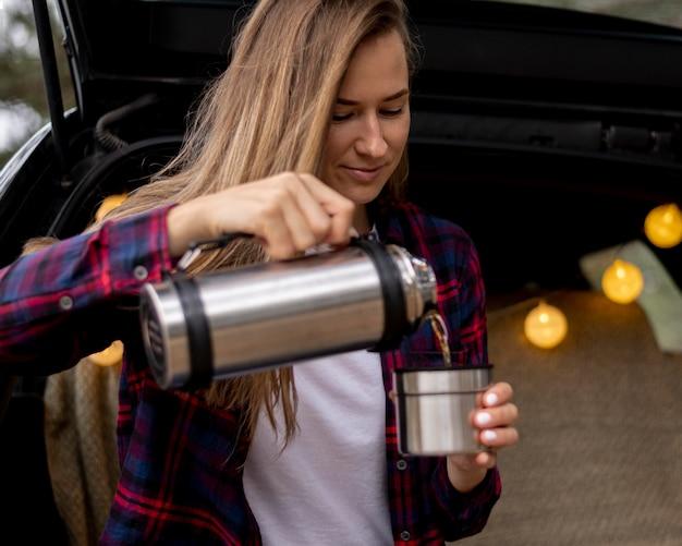 Hübsche junge frau, die kaffee einschenkt