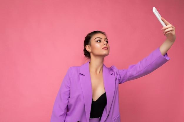 Hübsche junge frau, die lila anzug trägt selfie-konzept auf dem handy isoliert