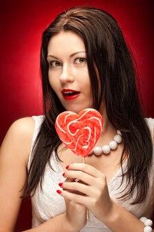 Hübsche junge frau, die lolly pop hält. über rotem hintergrund.
