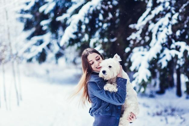 Hübsche junge frau, die mit ihrem weißen hund in einem winterpark spielt. entzückender verschneiter tag.