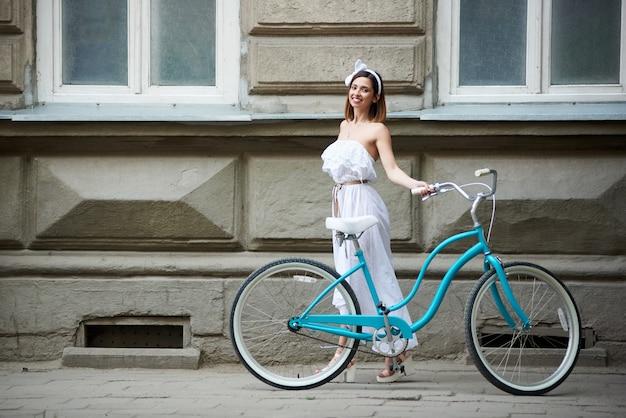 Hübsche junge frau, die mit klassischem blauem fahrrad mit altem historischem gebäude aufwirft