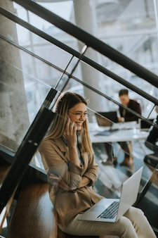 Hübsche junge frau, die mit laptop auf der treppe sitzt und handy im modernen büro vor ihrem team benutzt