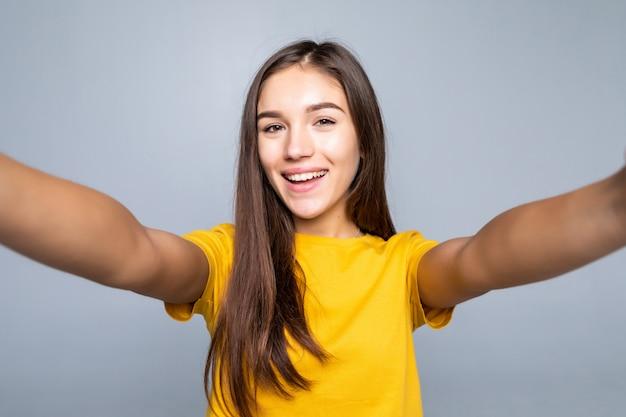 Hübsche junge frau, die selfie auf weißer wand macht