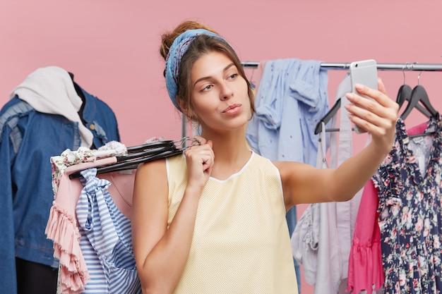 Hübsche junge frau, die selfie macht, während sie in der nähe von gestellen mit kleidern steht und froh ist, ihre freizeit im einkaufszentrum zu verbringen. entzückende dame, die modernes mobiltelefon beim einkaufen allein verwendet.