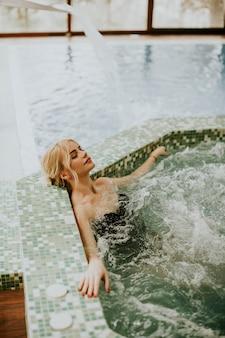 Hübsche junge frau, die sich in der whirlpool-badewanne entspannt