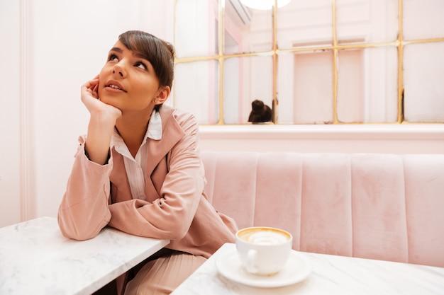 Hübsche junge frau, die sitzt und weg schaut auf kaffeetisch