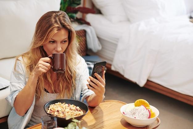 Hübsche junge frau, die social media auf dem smartphone überprüft, wenn sie ihr gesundes frühstück isst und zu hause kaffee trinkt