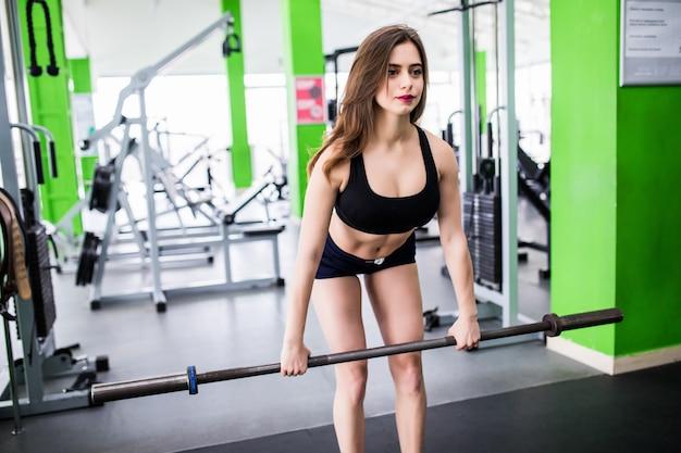 Hübsche junge frau, die übungen mit langhantel macht, die in modesportbekleidung im sportclub gekleidet sind